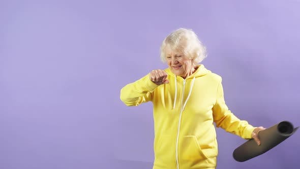 Stylish Granny in a Yellow Sports Sweater Holds a Yoga Mat and Moves To the Music.