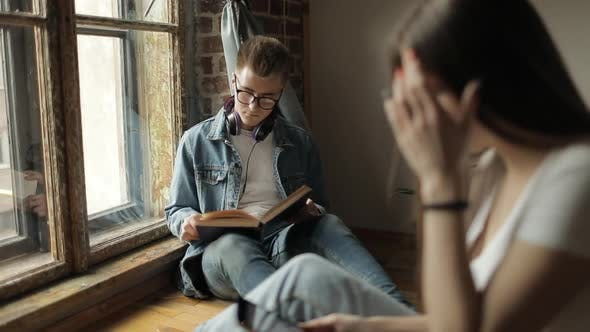 Thumbnail for Young Students Reading Book and Using Smartphone