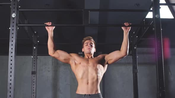 Thumbnail for Fitness Man Pumping Up Lats Muscles, Exercising Wide-grip Pull-up with Weight