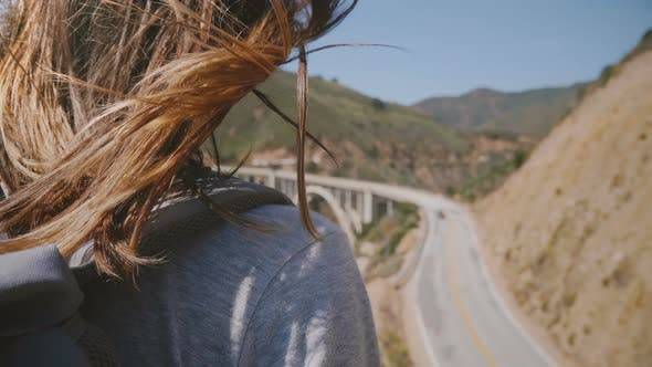 Thumbnail for Close-up Back View Shot of Young Woman with Hair Flying in the Wind Enjoying View of Highway One at