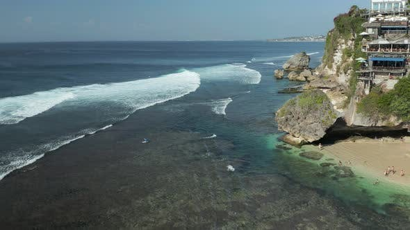 Aerial drone view of waves and surf off a small Balinese beach