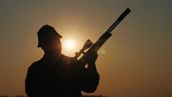 Thumbnail for Silhouette of a Hunter with a Gun, the Sun's Rays Shine in His Face