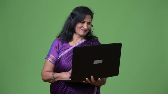 Thumbnail for Mature Happy Beautiful Indian Woman As Call Center Representative Using Laptop