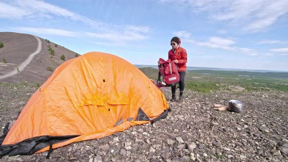 Thumbnail for Female Tourist Putting Stuff into Tent