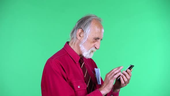 Portrait of Happy Old Aged Man 70s Communicates with Someone Texting on His Phone, Isolated Over