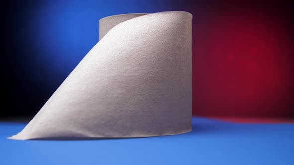 Grey Roll of Toilet Paper on Table Against Blue and Red