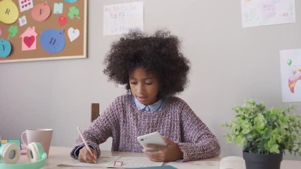Afrikanisches Schulmädchen mit Handy-App, der virtuelle Klasse zu Hause lernt