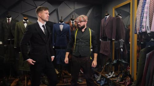 Tailor Dresses a Handsome Young Man in a Quality Handmade Suit in an Atelier. Creative Adult Stylist