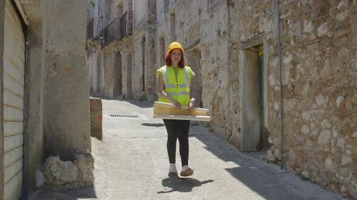 Young girl engineer with helmet checks a city after the earthquake