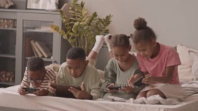 Kids Playing Games on Gadgets in Bed