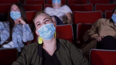 People in masks watch funny movie