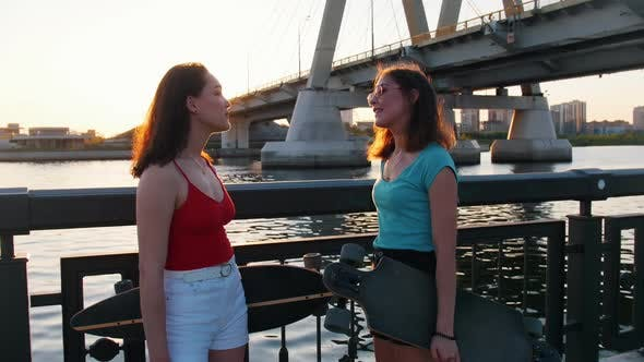 Thumbnail for Young Women Skateboarders Standing on the Waterfront and Talking - Sunset