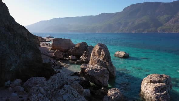 Spectacular Sea Landscape of Rocky Coast with Crystal Clear Water and Mountains in the Background
