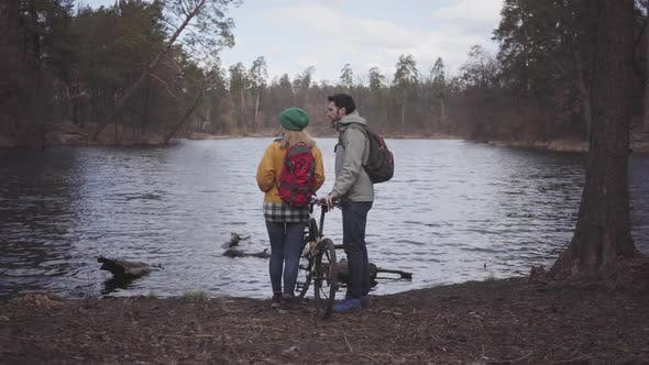 Cover Image for Young Couple of Tourists Standing on the Riverbank with Backpacks on Their Backs