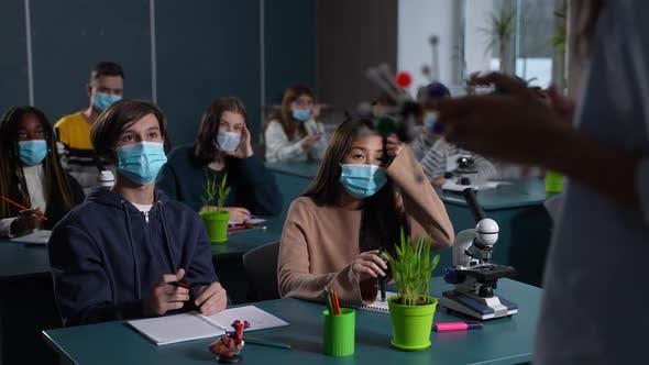 Masked Multiethnic Students Studying Chemistry