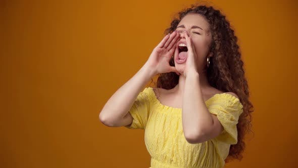 Young Curly Haired Woman Shouting Against Yellow Background