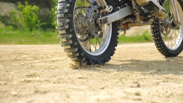 Close Up Wheel of Powerful Off-road Motorcycle Starting Movement and Kicking Up Dry Ground or Dust
