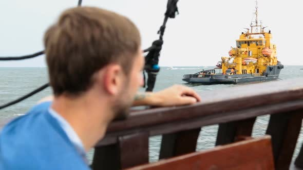 Thumbnail for Male Tourist Sailing on Pleasure Boat Past Barge Serving Oil Wells in Sea