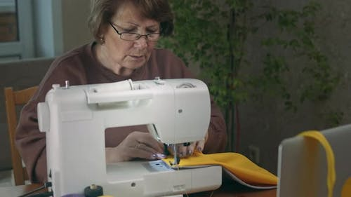 Female Tailor Using Sewing Machine.