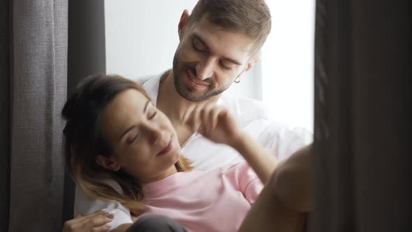 Thumbnail for Young Couple Is Sitting By the Window at Home. Husband or Boyfriend Hugs His Wife or Girlfriend