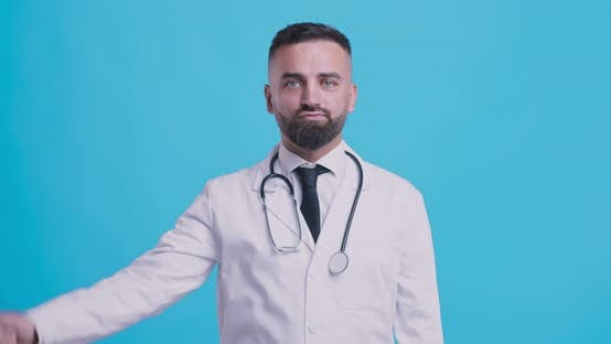 Thumbnail for Studio Portrait of Skeptical Medical Doctor Gesturing Thumbs Down with Both Hands, Blue Background