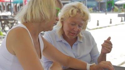Senior women in street cafe using smart watch