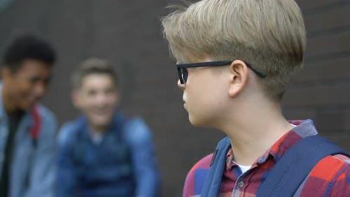 Gewalttätige Multirassische Schüler lachen Klassenkamerad in Brillen, Demütigung