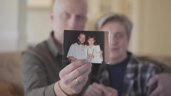 Thumbnail for Portrait of Senior Couple Showing Them Photograph To the Camera When Man and Woman Was Very Young