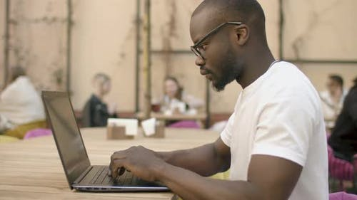 African-American Student Works on Laptop