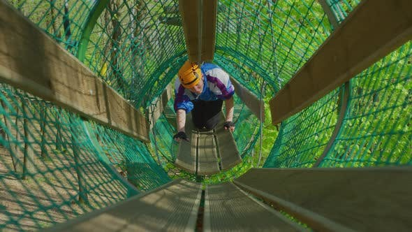 Man in a suspended net tunnel