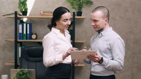 Mann und Frau schauen auf den Bildschirm des Tablets und führen die Diskussion