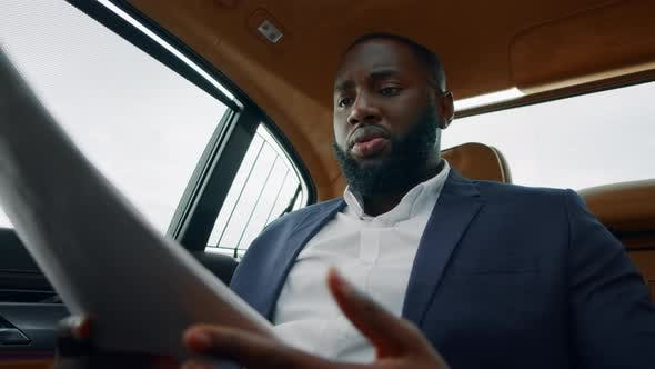 Thumbnail for Closeup African Man Reading Documents at Luxury Car. Businessman Throwing Papers