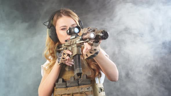 Girl Marksman in Sniper Gear Holding Sniper Rifle in Hand at Dark Smoky Background