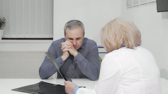 Thumbnail for Mature Man Listening Attentively To His Doctor at Medical Appointment