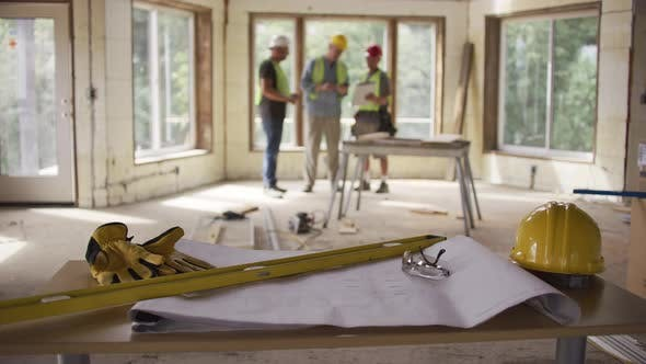 Thumbnail for Three construction workers looking over blueprints in background with foreground in focus