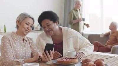 Senior Women Using Smartphone at Table