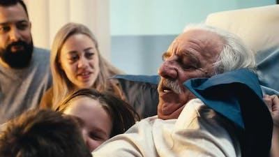 Aged Male Patient Hugging Grandchildren Near Parents