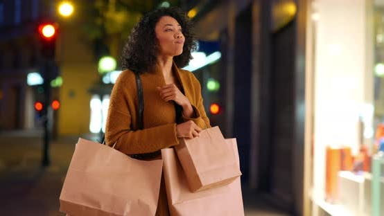 Thumbnail for Happy excited shopping woman with bags looking in store window