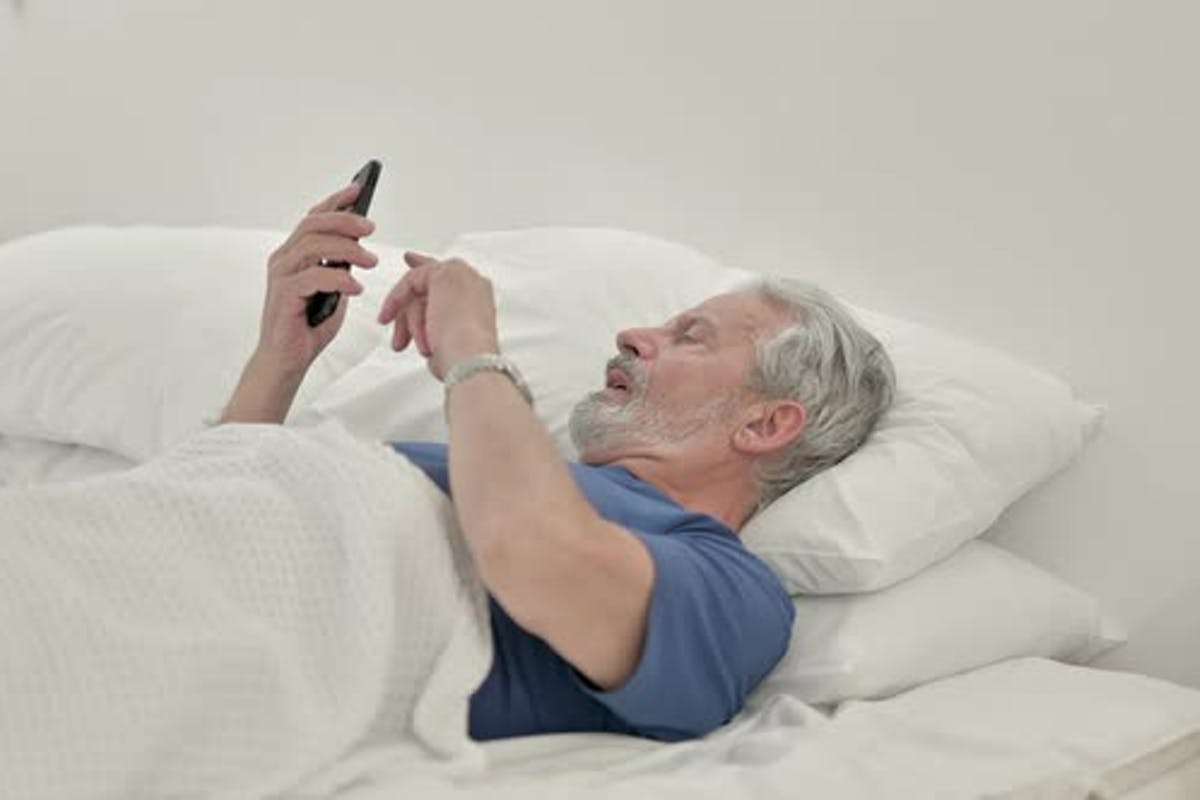 Angry Old Man Yelling On Phone Lying In Bed By Stockwood On