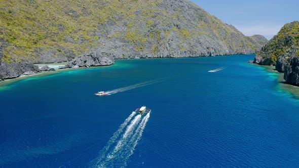 Thumbnail for Drone Follow Island Hopping Boats in Strait Between Matinloc and Tapiutan Island in El Nido, Palawan