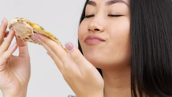 Japanese Young Lady Eating Hot Pizza Enjoying Taste White Background