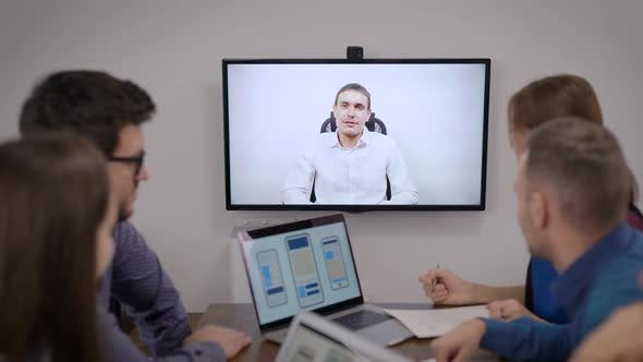 Thumbnail for Group of Specialists Are Having Video Conference with Boss in Office Room, Looking at Display