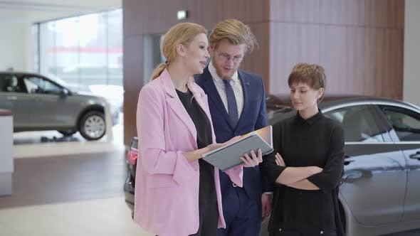 Thumbnail for Pleasant Woman in Pink Jacket Showing Information in Book To Customers - Professional Saleswoman