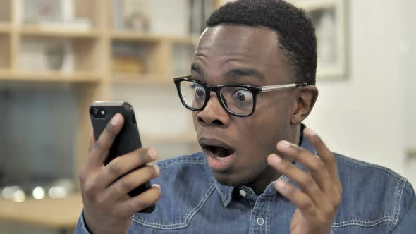 Thumbnail for Afro-American Man Reacting to Loss on Smartphone