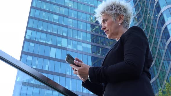 Thumbnail for A Middle-aged Businesswoman Works on a Smartphone in an Urban Area - a Windowed Office Building