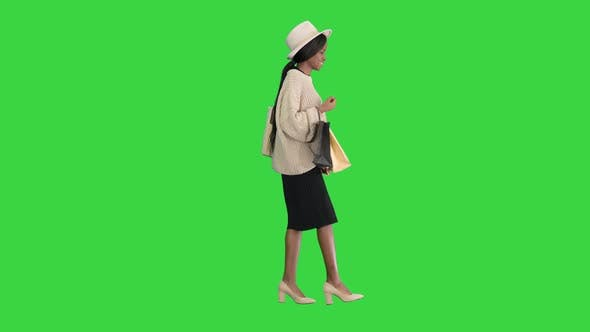 Thumbnail for Happy African American Woman in Hat and Knitwear Walking with Shopping Bags on a Green Screen