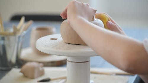 Close-up of Potter Making Pot in Pottery Workshop. Using Sponge and Water for Moisturizing Clay.