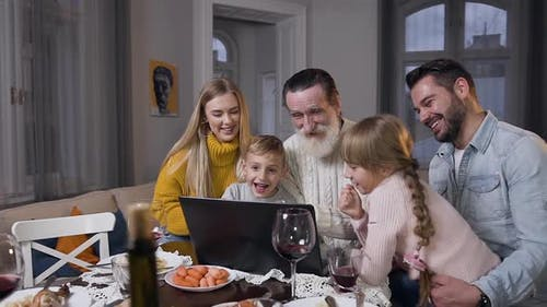 Family Watching Beautiful Photos on Computer which Showing them Respected Senior Grandpa