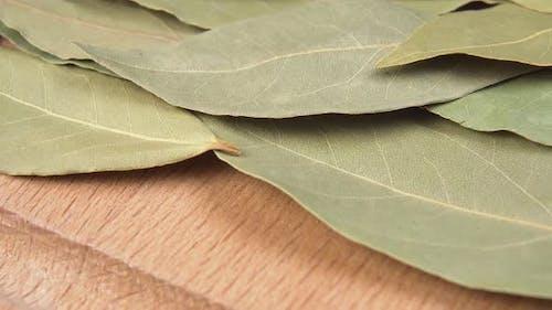 Seasoning bay leaf on a wooden surface macro shot.