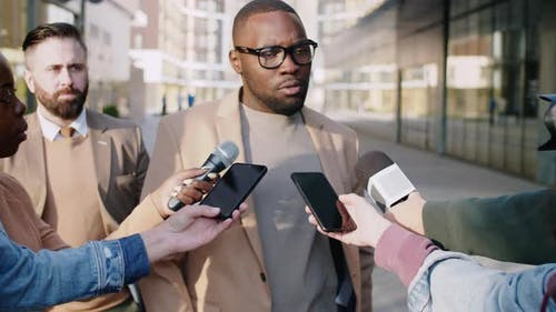 Black Man Giving Interview to TV Correspondents on Street
